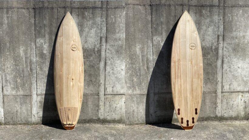 Holz-Surfboard in Vorder- und Rückansicht vor Betonmauer